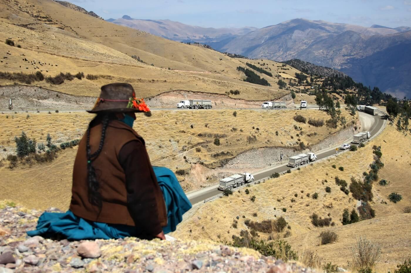 IMPACTOS. Una mujer quechua, en Challhuahuacho (Apurímac), observa la fila de camiones de Las Bambas.